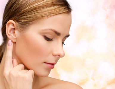 health and beauty concept - face of beautiful woman touching her ear