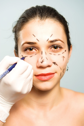 Drawing lines on a pretty Caucasian girl's face as marks for facial plastic surgery
